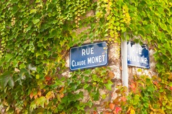 Close up of street signs on ivy covered walls at the corner of Rue Claude Monet (named after the famous impressionist painter who lived in the town) and Rue De La Dime in Giverny, France.