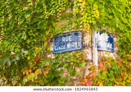 Close up of street signs on ivy covered walls at the corner of Rue Claude Monet (named after the famous impressionist painter who lived in the town) and Rue De La Dime in Giverny, France. Photo stock ©