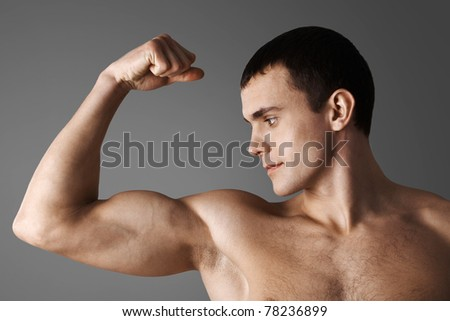 Close-up of strong muscular man over grey background