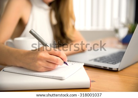 Close up of student business woman hand laptop computer taking notes studying at home