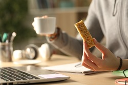 Close up of student girl hands holding coffee cup and cereal snack bar at night studying