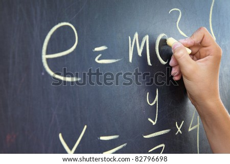 Close-up of student?s hand writing physics formula on blackboard
