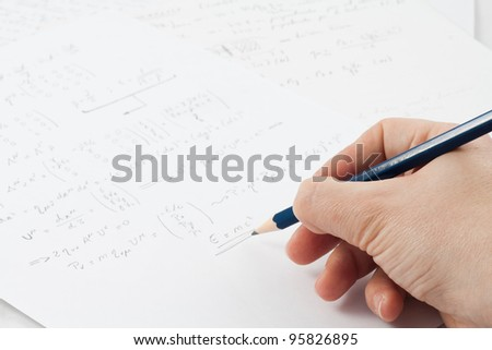 Close-up of student's hand writing physics formula on paper