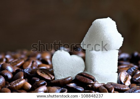 Close up of sugar hearts surrounded by roasted coffee beans