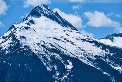 Close-up of summit of Tantalus Peak with jagged rock outcrops, snow, glaciers and the upper reaches of forest.  Between Squamish and Whistler, BC.