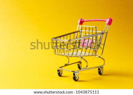 Close up of supermarket grocery push cart for shopping with black wheels and red plastic elements on handle isolated on yellow background. Concept of shopping. Copy space for advertisement. #1043875111