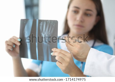 Close-up of surgeon hands holding wrist skiagram. Serious woman in medical uniform consulting with colleagues about trauma. Traumatology and healthcare concept Stock photo ©