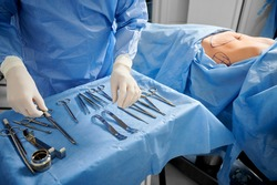 Close up of surgeon in sterile gloves getting ready medical instruments. Female patient with marks on skin lying on medical bed while doctor preparing tools. Concept of plastic surgery preparation.