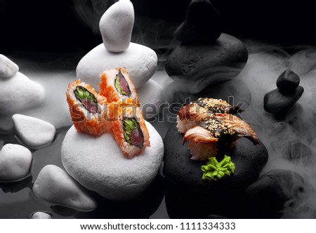 Close up of sushi nigiri with eel and sushi maki California set .Sushi. On dark stone with fog .Creative shot. Japanese athmophere.Copy space.Concept sushi maki versus nigiri.Ying and yang