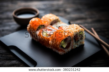 close up of sushi rolls on black tray
