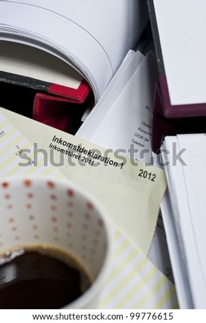 Close up of swedish tax declaration form and some documents and binders and a cup of coffee
