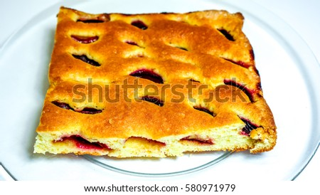 close up of sweet homemade cake with fruit fresh plumps and texture-baked dough cut into square against clear glass plate. Peace of home holiday cake as best addition to a cup of coffee or tea