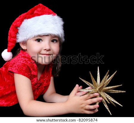 close-up of sweet little girl in santa hat laying on floor with golden star. isolated