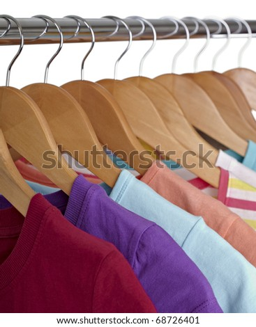 close up of t shirts on cloth hangers in row