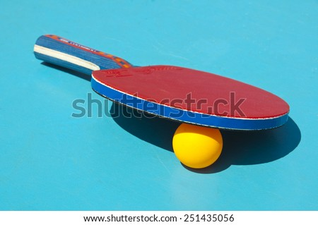 Close up of table tennis racket and ball on a blue table