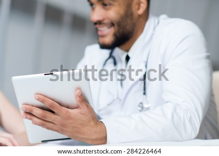 Close up of tablet. Doctor in white medical clothes is holding tablet in hospital. Medical concept.