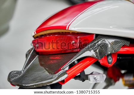 Close up of taillight detail of modern luxury sports bike with reflection on paint after wash & wax. Rear view of shiny superbike with mudguard. Concept of car detailing. Automotive background. #1380715355