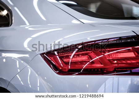 Close up of taillight detail of modern luxury sportscar with reflection on white paint after wash & wax. Rear view of supercar break lights. Concept of car detailing and paint protection background. #1219488694
