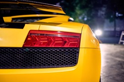 Close up of taillight detail of modern luxury sportscar with reflection on yellow paint after wash & wax. Rear view of supercar. Concept of car detailing and paint protection background. Night shot.