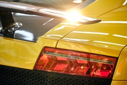 Close up of taillight of modern luxury sportscar with sunlight reflection on spoiler. Shiny yellow paint after wash & wax. Rear view of supercar. Concept of car detail and paint protection background.