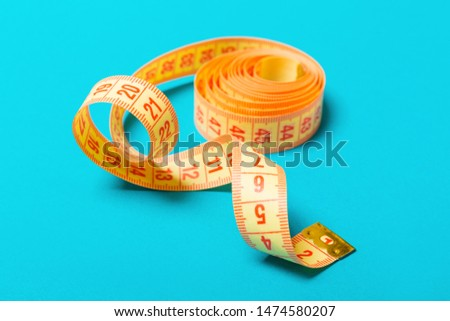 Close up of tangled measuring tape on blue background. Fitness and healthy diet concep with perspective view.