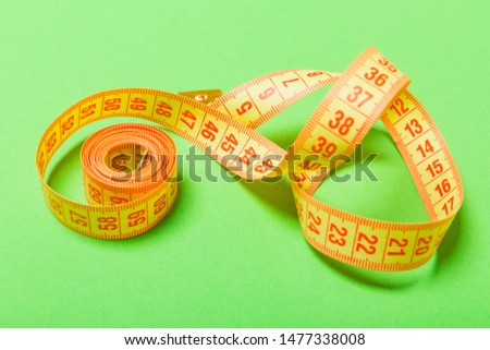 Close up of tangled measuring tape on green background. Fitness and healthy diet concep with perspective view.