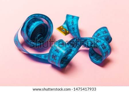 Close up of tangled measuring tape on pink background. Fitness and healthy diet concep with perspective view.