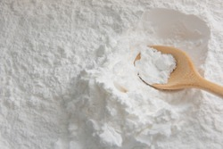 Close-up of tapioca starch or flour powder in wooden spoon with wooden background