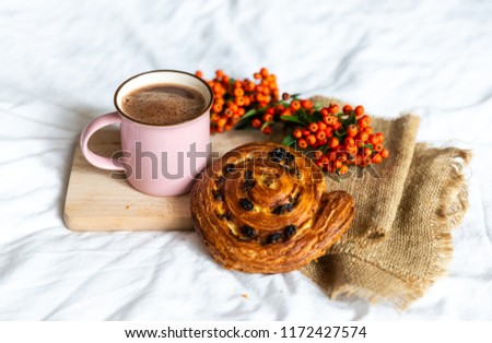 Close up of tasty and delicious breakfast in bed with cake and cacao. Fresh bake and coffee in pink cup on wooden board, near orange autumn berries. Concept of autumn morning. #1172427574
