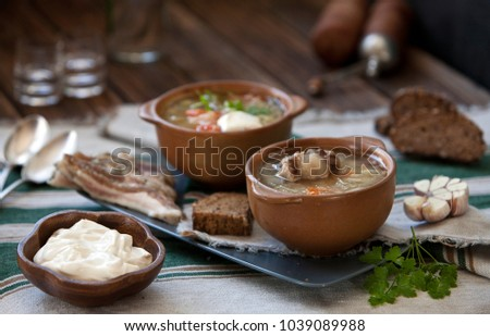 Close-up of tasty russian cabbage soup shchi in brown ceramic bowls on wooden table. Close-up, selective focus, shallow depth of field #1039089988