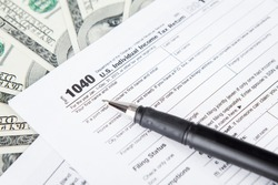 Close up of tax forms with dollar bills and pen