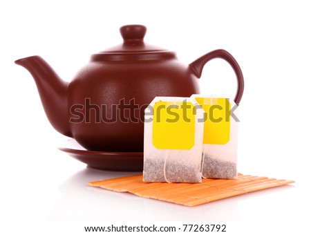 Close-up of tea bag and teapot isolated on white background