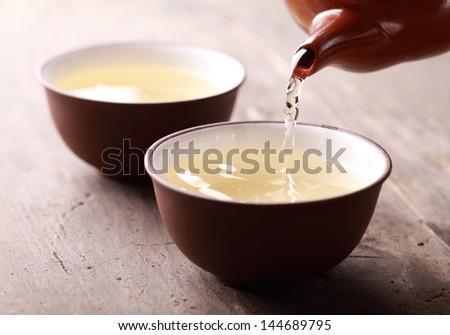 Close-up of tea pot ant tea pouring into bowl.