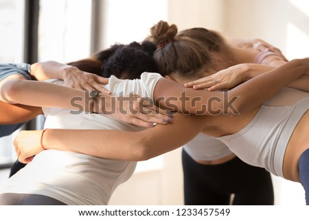Close up of team diverse girls embracing standing in circle having motivational pep talk before match indoors. Multi-ethnic females congratulating each other after sports training hugging feels happy