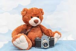 Close-up of teddy bear stuffed toy sitting with old vintage photocamera on blue wooden surface. Blue sky pastel background. Photography, grunge and retro style concept