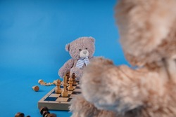 Close up of teddy bears with chess pieces on chessboard. Soft plush toys playing chess on blue background