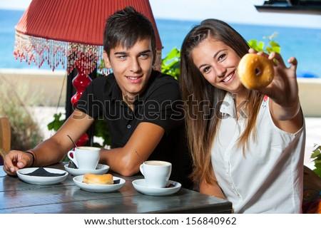 Close up of teen couple having breakfast at seaside.