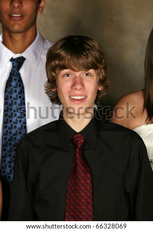 close up of teen guy in tie singing in a group