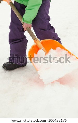 Close Up Of Teenage Boy Shovelling Snow From Path