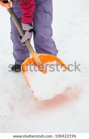 Close Up Of Teenage Girl Shovelling Snow From Path