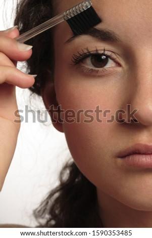 Close-up of teenage girl with eyebrow brush
