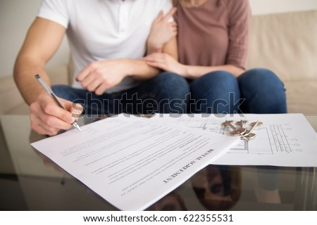 Close up of tenants signing rental agreement, renters couple sitting on couch, male hand with a pen putting signature, focus on document and keys, joint residential tenancy, lease contract