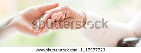 Close-up of tender gesture between two generations. Young woman holding hands with a senior lady. Blurred background. Panorama.