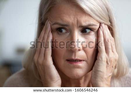 Close up of terrified mature woman look in distance thinking remembering, scared senior female retiree grandmother feel scared frightened, face strong fear or anxiety at home, having panic attack ストックフォト ©