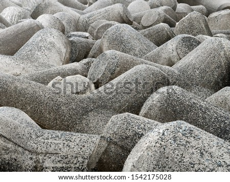 Close-up of Tetra-pods concrete breakwaters to protecting sea coastal structures from destructive impact of storm sea waves, shows as abstract texture breakwaters barrier background. #1542175028