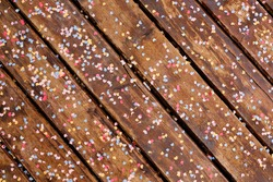 Close-up of textured brown wooden planks strewn with multicolored confetti in the shape of the moon and stars.