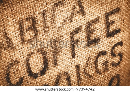 Close up of textured woven hessian fabric with the word Coffee stamped on it in a coffee background concept