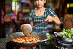 close up of thai woman cooking red spicy chicken curry in wok