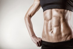 Close-up of the abdominal muscles young athlete on gray background