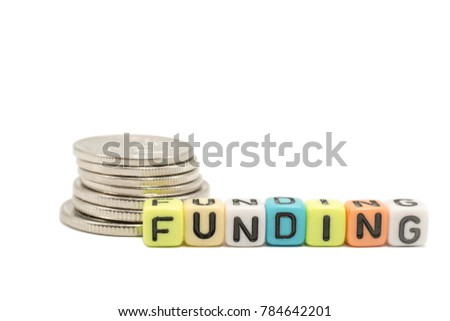 Close up of the alphabet dice of a word FUNDING and stack of coins, isolated on with background with clipping path added. This is for the concept of money, finance, funding and business.